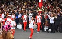 聖火を手に走るインドネシアのジョコ・ウィドド大統領(中央)=ジャカルタのムルデカ宮殿で2018年8月17日午後4時22分、徳野仁子撮影