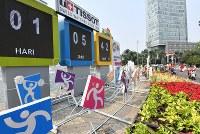 市中心部に設置されたアジア大会開幕までのカウントダウンボード。右奥はインドネシアの独立記念日を祝福しながらバイクなどで走る人たち=ジャカルタで2018年8月17日、宮間俊樹撮影