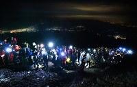 午前3時過ぎ、あと1時間半後に迫ったご来光を富士山頂で眺めようと、ヘッドライトをつけた大勢の登山者らで大渋滞となった登山道。左奥の明かりは富士吉田市の中心部=吉田口9合目で2018年7月16日、手塚耕一郎撮影