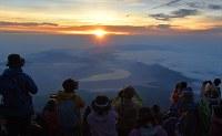 山中湖(中央)の奥から昇るご来光を眺める登山者=富士山頂で2018年7月16日、手塚耕一郎撮影