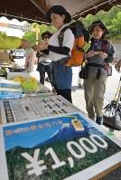 富士スバルライン5合目で、世界遺産登録後に始まった富士山保全協力金(入山料)を支払う登山者。現在、任意での協力を呼びかけていて回収率は6割前後だという。登山期間中、5合目では24時間態勢で受付を設置している=山梨県鳴沢村で2018年7月14日、手塚耕一郎撮影