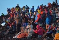 防寒着を着込み、ご来光の写真を撮る大勢の登山者=富士山頂で2018年7月16日、手塚耕一郎撮影