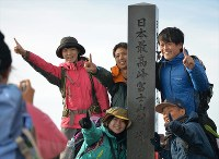 日本最高地点となる富士山剣ケ峰(標高3776メートル)の石碑前で、記念撮影する登山者ら=2018年7月16日、手塚耕一郎撮影