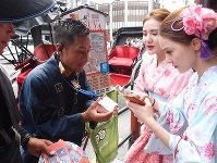 Two Chinese tourists, right, pay for a rickshaw ride using the smartphone payment app Alipay, in the Asakusa district of Tokyo's Taito Ward, on Aug. 11, 2018. (Mainichi)