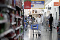 In this Nov. 9, 2017 file photo, a man pushes a cart while shopping at a Walmart store in North Bergen, New Jersey. (AP Photo/Julio Cortez)