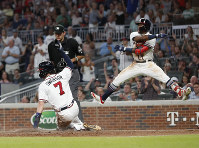 Atlanta Bravess Ronald Acuna Jr. reacts as Dansby Swanson (7) scores on a Julio Terheran base hit during the fifth inning of a baseball game against the Colorado Rockies, on Aug. 16, 2018, in Atlanta. The Rockies won 5-3. (AP Photo/John Bazemore)