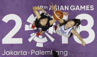 Combined Koreas' Ro Suk Yong, left, and Taiwan's Hsile Bao jump for ball possession during their women's basketball match at the 18th Asian Games in Jakarta, Indonesia, on Aug. 17, 2018. (AP Photo/Aaron Favila)