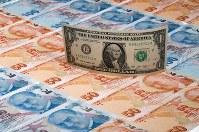 8月16日、トルコで、エルドアン大統領の呼びかけに応じてドルを売った市民らに、店舗などがサービスのお返しを贈る動きが広がっている。写真はドル紙幣(中央)とリラ紙幣(2018年 ロイター/Murad Sezer)