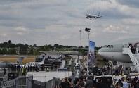 デモ飛行では各社の新鋭機が急上昇や急旋回を繰り返し、滑走路上の見物客の視線をくぎづけにした=英南部ファンボローで7月16日、三沢耕平撮影