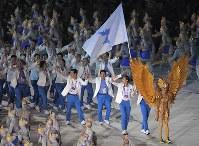 神鳥「ガルーダ」の衣装を着た女性に先導され、「統一旗」を掲げて入場行進する韓国と北朝鮮の選手団=ジャカルタのブンカルノ競技場で2018年8月18日、徳野仁子撮影