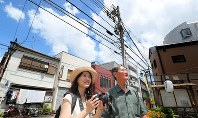 Tsutomu Sato, right, walks around an area where his father Tomigoro was working as a bus driver, with Shiori Okawa, in Tokyo's Toshima Ward on July 29, 2018. Sato was born here but he has no memory of it. (Mainichi)