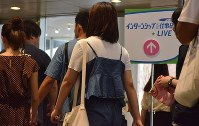 University students enter the venue for a job research seminar organized by Recruit Co. in Saitama in July 2018. (Mainichi)