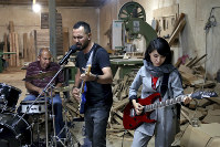 In this July 20, 2018 photo, members of the rock band Arikayn, Afghan musicians Hakim Ebrahimi, center, and Soraya Hosseini, right, play with Kourosh Ghasemi, an Iranian drummer, at a furniture workshop in Eslamshahr, on the outskirts of Iran's capital, Tehran. (AP Photo/Ebrahim Noroozi)
