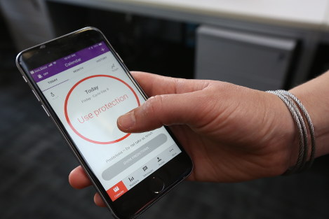 A woman demonstrates using the Natural Cycles smartphone app, in London, on Aug. 17, 2018. The mobile fertility app has become the first ever digital contraceptive device to win FDA (US Food and Drug Administration) marketing approval, enabling women to track their menstrual cycle and uses an algorithm to determine when they're fertile, and need to use birth control protection. (AP Photo/Nishat Ahmed)