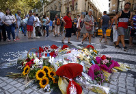 People stand next to a memorial tribute of flowers, messages and candles on Barcelona's historic Las Ramblas in Barcelona, on Aug. 16, 2018, the day before to the anniversary of the attacks that took place here on Aug. 17, 2017 killing 16 people and injuring more than 120. (AP Photo/Manu Fernandez)