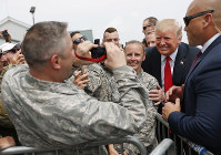President Donald Trump poses for photographs while greeting members of the military on the tarmac upon his arrival on Air Force One at Francis S. Gabreski Airport in Westhampton, N.Y., on Aug. 17, 2018. (AP Photo/Pablo Martinez Monsivais)
