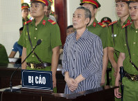 Activist Le Dinh Luong, center, stands trial in the central province of Nghe An, Vietnam, on Aug. 16, 2018. (Bich Hue/Vietnam News Agency)