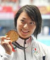 競泳女子100メートル平泳ぎで優勝し、金メダルを手にする鈴木聡美=ジャカルタで2018年8月19日、宮間俊樹撮影
