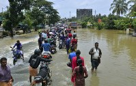 People move past a flooded road in Thrissur, in the southern Indian state of Kerala, Friday, Aug. 17, 2018. (AP Photo)