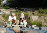 10人が犠牲になった八木ケ丘団地。災害当時、町内会長を務めた奥迫信治さん(左)は流された住宅跡で手を合わせ、「あの日はいまだに忘れられん。砂防ダムができても用心しないといけない」と話した=広島市安佐南区で2018年8月20日午前6時48分、山田尚弘撮影