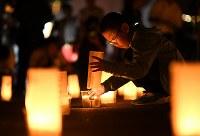 土砂災害から4年を迎え、キャンドルを並べる永田俊太郎さん。親戚の家が流されたといい、「思いを込めて並べました」=広島市安佐南区で2018年8月20日午前3時51分、久保玲撮影