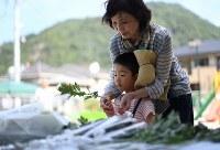 土砂災害から4年を迎え、孫の今田伝さん(5)と慰霊碑に献花する妙子さん(67)。伝さんと参列したのは初めてだといい、「孫と同じくらいの子供も犠牲になった。大きくなったらここで大災害があったことをちゃんと伝えたい」と話した=広島市安佐北区で2018年8月20日午前9時32分、久保玲撮影