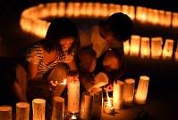 犠牲者を悼み、紙灯籠に火をともす人たち=広島市安佐南区で2018年8月20日午後7時28分、久保玲撮影