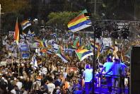 ユダヤ人国家法に反対するデモ会場ではドルーズ旗とイスラエル国旗が入り乱れ、「平等」のスローガンが叫ばれた=テルアビブで2018年8月4日夜、高橋宗男撮影
