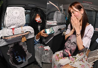 A driver hands a box of cool body wipes to a passenger in a