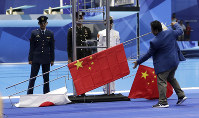 The flags of China and Japan fall during the medal ceremony for the men's 200m freestyle during the swimming competition at the 18th Asian Games in Jakarta, Indonesia, on Aug. 19, 2018. (AP Photo/Lee Jin-man)