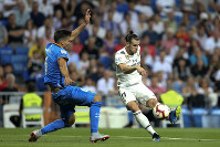 Real Madrid's Gareth Bale, right, shoots the ball next to Getafe's Leandro Cabrera during a Spanish La Liga soccer match at the Santiago Bernabeu stadium in Madrid, on Aug. 19, 2018. (AP Photo/Andrea Comas)