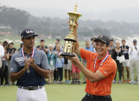 Viktor Hovland, right, of Norway, holds up the Havemeyer Trophy on the 13th green of the Pebble Beach Golf Links after winning the USGA Amateur Golf Championship on Aug. 19, 2018, in Pebble Beach, Calif. Hovland won the match against Devon Bling, left. (AP Photo/Eric Risberg)