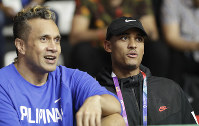Filippino-American NBA player Jordan Clarkson, right, watches with Philippines' Pauliasi Taulava on the bench as he arrives during a match between the Philippines and Kazakhstan at the men's basketball event at the 18th Asian Games in Jakarta, Indonesia, on Aug. 16, 2018. (AP Photo/Aaron Favila)