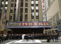 In this April 17, 2018 photo, Mayor's Office of Media and Entertainment commissioner Julie Menin, center, Darren Pfeffer, executive vice president of MSG live, left, and Bruce Gillmer, global head of music/talent MTV International announce the MTV VMAs' return to New York City and symbolic street renaming outside Radio City Music Hall in New York. (Photo by Evan Agostini/Invision/AP)