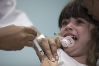 In this Aug. 6, 2018 photo, a child receives a measles vaccination in Rio de Janeiro, Brazil. (AP Photo/Leo Correa)