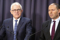 Australian Prime Minister Malcolm Turnbull, left, and Environment Minister Josh Frydenberg address reporters at Parliament House in Canberra, Australia, on Aug. 20, 2018. (AP Photo/Rod McGuirk)