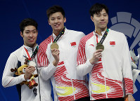 Men's 200m individual medley gold medalist China's Wang Shun, centre, stands with silver medalist Japan's Kosuke Hagino, left, and bronze medalist China's Qin Haiyang on the podium during the swimming competition at the 18th Asian Games in Jakarta, Indonesia, on Aug. 20, 2018. (AP Photo/Bernat Armangue)