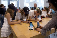 In this Aug. 2, 2018, file photo customers browse in an Apple store in New York. (AP Photo/Mark Lennihan)