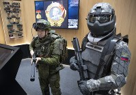A man, left, wears a working sample of a passive exoskeleton combat gear, next to a mannequin dressed in a prototype of an active exoskeleton combat gear presented by the Russian Rostec company during the International Military Technical Forum Army-2018 in Alabino, outside Moscow, on Aug. 21, 2018. (AP Photo/Pavel Golovkin)