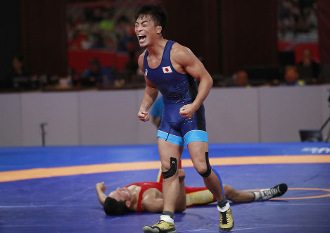 Japan's Ota Shinobo, center, celebrates after defeating Kazakhstan's Kov Kanybek Zholchube during their men's Greco-Roman 60-kilogram final wrestling match at the 18th Asian Games in Jakarta, Indonesia, on Aug. 21, 2018. (AP Photo/Tatan Syuflana)