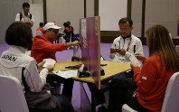 In this Aug. 21, 2018 photo, bridge players, from left to right, Mariko Ueda of Japan, George Mondigir of Indonesia, Tetsuya Ueda of Japan and Elvita Lasut of Indonesia play during a bridge competition game at the 18th Asian Games in Jakarta, Indonesia. (AP Photo/Firdia Lisnawati)