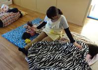 お昼寝で子どもを寝かしつけるスタッフ。夜間は一人で8人の面倒を見ることもある=長野県上田市のうえだみなみ乳児院で