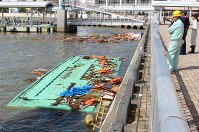屋根だけを海上に出した状態で沈んだ2隻の屋形船(手前と奥)=神戸市中央区波止場町の神戸港中突堤中央ターミナルで2018年8月24日午前9