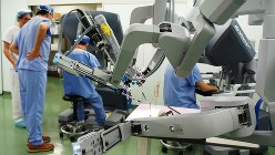ダヴィンチのアーム部分。奥に二つある操作台で医師らがアームを操る訓練をしている=弘前市の弘前大医学部付属病院で2013年12月11日、伊藤奈々恵撮影