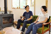 自慢のまきストーブの前でくつろぐ中森千亜季さん(右)と健二さん=長野県原村の自宅で、村瀬優子撮影