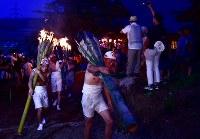 たいまつを担いで麓山を駆け上がる氏子たち=福島県富岡町で2018年8月15日、竹内紀臣撮影
