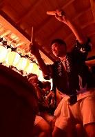 やぐらの上で盆踊りの太鼓をたたく佐藤智之さん。2011年の3月、震災の直前に青年会会長になった。「8年も会長しているのは俺だけでしょ」と笑いながらも、準備の先頭に立ってきた=福島県富岡町の麓山神社で2018年8月15日、竹内紀臣撮影