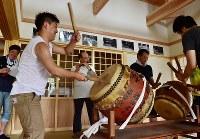 坂本仁さん(中央)に教えてもらいながら、盆踊りの太鼓、笛、唄を練習する新田泰大さん(左手前)ら青年会のメンバー=福島県富岡町の麓山神社で2018年7月21日、竹内紀臣撮影