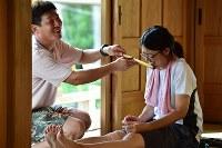 盆踊りの太鼓、笛、唄は聞いて、見て覚えるもの。佐藤智之さん(左)から笛の指導を受ける鈴木那緒さん(28)=福島県富岡町の麓山神社で2018年8月12日、竹内紀臣撮影