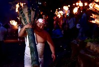 たいまつを担いで麓山を駆け上がる青年会の伊藤和之さん=福島県富岡町で2018年8月15日、竹内紀臣撮影